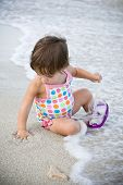 Girl Playing With The Waves And The Sand