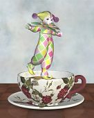 stock photo of clown rose  - Cute Pierrot style clown doll from traditional French pantomime in harlequin suit balancing on the edge of a tea cup - JPG