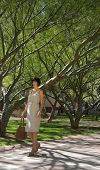 Attractive Professional Woman Walking Through Park With Beautiful Trees