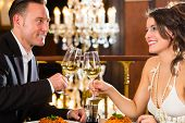happy couple have a romantic date in a fine dining restaurant they drink wine and clinking glasses,