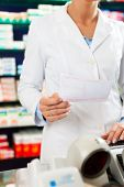 Female Pharmacist in pharmacy, standing at the cashier she is holding a prescription slip in her hands