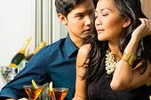 pic of minx  - Asian man and woman in flirting intimately at bar drinking cocktails - JPG