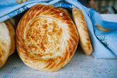 Traditional eastern lepeshka nan - white flat bread baked in old stove