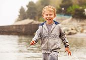 Cute Smiling Little Boy Run In Water Drops