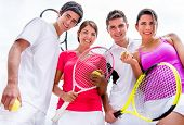 Group of friends playing tennis outdoors and looking very happy