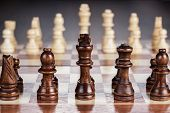stock photo of battle  - chess board with figures on the brown table background - JPG