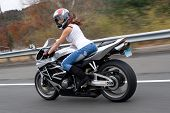 picture of crotch-rocket  - A pretty blonde girl in action driving a motorcycle at highway speeds - JPG