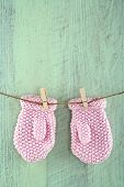 Mittens On Clothesline On Green Vintage Wooden Background