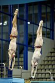 MOSCOW - APR 13: Athletes jump from diving-tower at competitions on syncronized springboard diving i