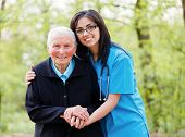 stock photo of sitting a bench  - Portrait of caring nurse helping elderly lady holding her hands - JPG
