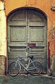 Vertical oriented image of bicycle leaning against old wooden door at the entrance to house on rainy