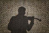 Silhouette of a violin player against brick wall