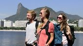 Group of tourist backpackers friends  walking through Rio de Janeiro with Christ the Redeemer in background.