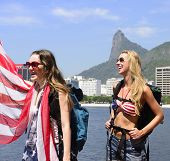 Sport fans holding USA Flag in Rio de Janeiro with Christ the Redeemer in background.