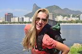 Happy blond young backpacker woman traveling at Rio de Janeiro with the Christ Redeemer in backgroun
