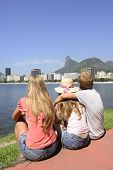 Group of tourists friends sitting on the edge of Guanabara Bay watching the Christ the Redeemer.