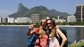 Couple of female backpackers making a self portrait in Rio de Janeiro with Christ the Redeemer in ba