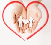 family, love and happiness concept - mans hands showing two paper men with heart shape