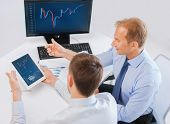 business, money and office concept - businessmen with notebook and tablet pc discussing forex chart on meeting