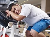 stock photo of obese man  - an overweight young man exhausted with exercising in fitness center - JPG
