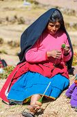 Puno, Peru - July 25, 2013: woman weaving in the peruvian Andes at Taquile Island on Puno Peru at july 25th, 2013. The highest point of the island is 4050 masl and the main village is at 3950m