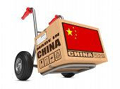 stock photo of slogan  - Cardboard Box with Flag of China and Made in China Slogan on Hand Truck White Background - JPG