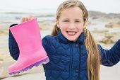 Portrait of a cute smiling young girl holding her wellington boot at the beach