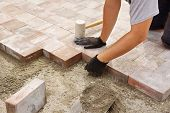 stock photo of trade  - Man or trade worker installing paver stone in the backyard