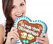 picture of scandinavian descent  - Attractive woman bites into gingerbread heart from the Octoberfest - JPG