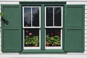 Pots of flowering geraniums in the window of Green Gables House, made famous by the Anne of Green Gables books by L. M. Montgomery.  Located in Cavendish, Prince Edward Island, Canada.