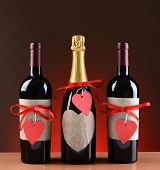 Champagne and wine bottles decorated for Valentines Day. The bottles have red ribbons and heart shap