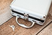 Aluminum Opened Suitcase With Keys On Wooden Floor