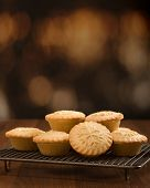 Homemade traditional mince pies on cooling rack with snowflake decoration