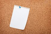 Blank notepad paper on cork wood notice board with copy space