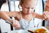 Adorable little girl eating breakfast in restaurant