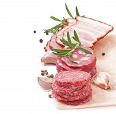 Assorted deli meats, rosemary and pepper, isolated on white