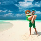 Couple in green on a tropical beach at Maldives. Man in holding woman on his arms.