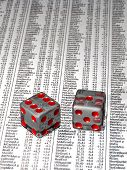 Two dice over stock market quotes - shallow depth of field with focus on the dice