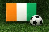 Flag of the Ivory Coast with soccer ball over grass background - very highly detailed render