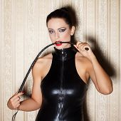stock photo of latex woman  - Sexy woman in latex catsuit with whip in mouth desire - JPG