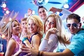 Portrait of glamorous girls dancing at party with happy friends near by