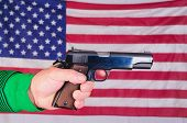 Close-up of a Left-handed shooter holding semi-automatic pistol in front of a US flag