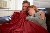 Couple Trying To Keep Warm Under Blanket At Home