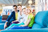 Family selecting together sofa in home-centre to furniture store