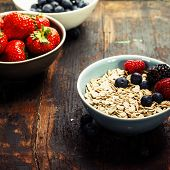 Bowls with cereals and fresh berries on wooden table