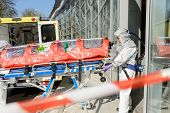 Biohazard medical team member with stretcher entering contaminated building
