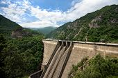 image of hydroelectric  - Hydroelectric equipment concrete dam wall on clouds sky background - JPG