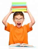 Little boy is holding a pile of books and showing aggressive grimace, isolated over white