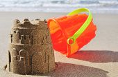 an orange toy bucket and a sandcastle on the sand of a beach