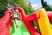 stock photo of castle  - Small boy jumping down the slide on an inflatable bouncy castle - JPG